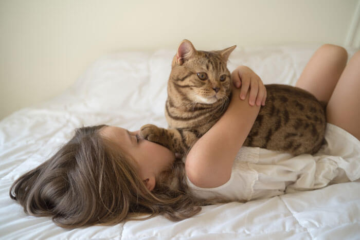a girl hugging a cat
