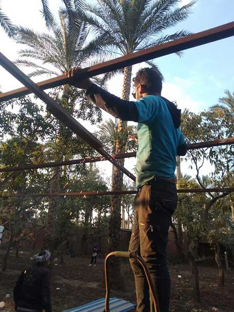 Animal rescuer constructing a new shelter structure in egypt.