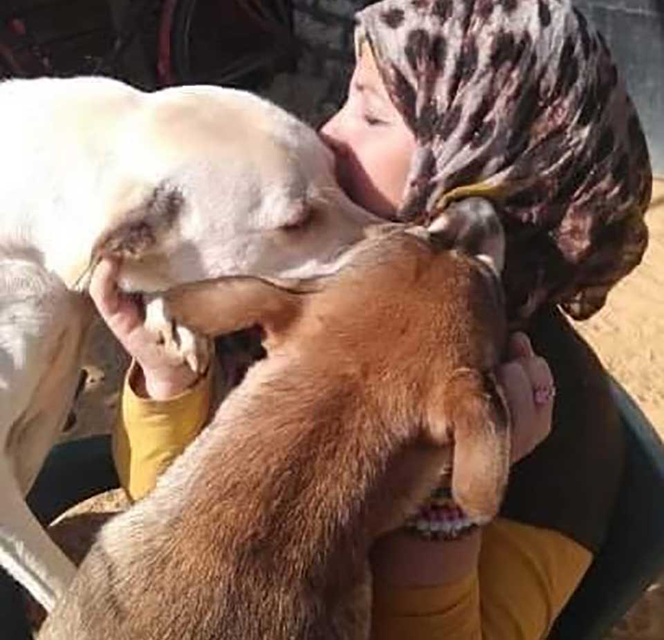 Animal rescuer, Hoda Mklad embracing her rescue dogs in Egypt.